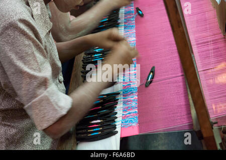 Hands of a woman weaving by using shuttles with thread spools on a loom. Partially woven silk fabric visible. Mandalay, - Stock Photo