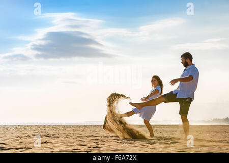 Happy newlywed family on honeymoon holidays - just married loving wife and husband run with fun on sea sand beach. - Stock Photo