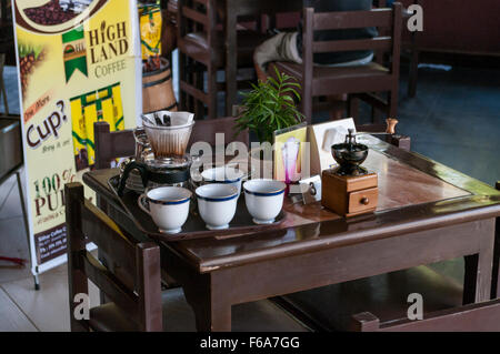 Set to prepare freshly brewed coffee in a cafe in Pyin Oo Lwin, Myanmar, consisting of cups, a coffee grinder and - Stock Photo
