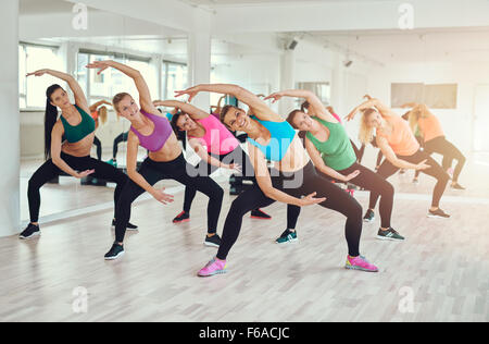 Aerobics class at a gym with a group of attractive fit young women in colorful sportswear working out in synchronisation, - Stock Photo