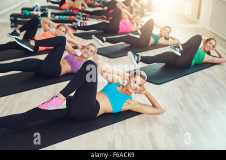Group of fit healthy young women in a gym wearing colorful sportswear working out in an aerobics class in a healthy - Stock Photo