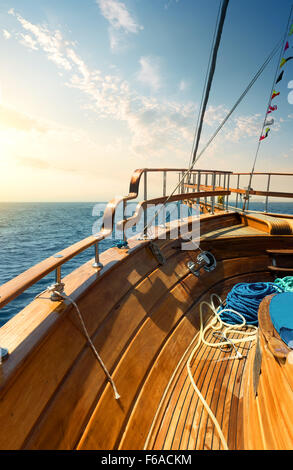 Wooden sailboat in turquoise sea at sunset - Stock Photo