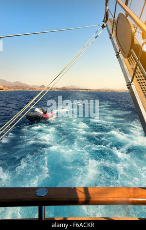 Wooden sailboat tows rubber boat in the sea - Stock Photo