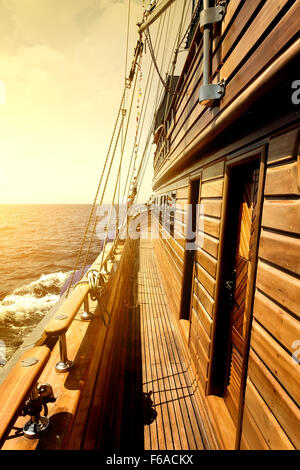 Wooden sailboat in sea at the bright sunrise - Stock Photo
