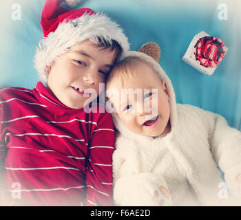 Two brothers, one and six years old in santa, bear costumes - Stock Photo