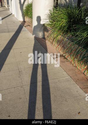 A long shadow of a photographer as a self-portrait along a sidewalk in Santa Barbara, California. - Stock Photo