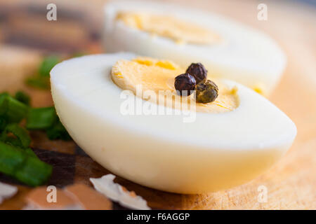 Half of boiled egg  prepared on cutting board with grains of pepper - Stock Photo