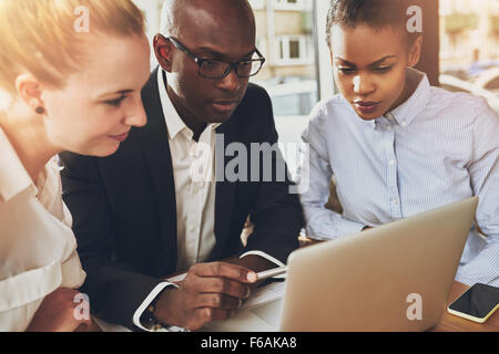 Multi ethnic business people working at office sitting in front of a laptop, black business woman, white business woman