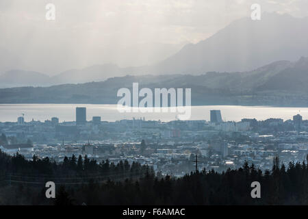 The Swiss city of Zug with Lake Zug and the Swiss mountains in the background. - Stock Photo