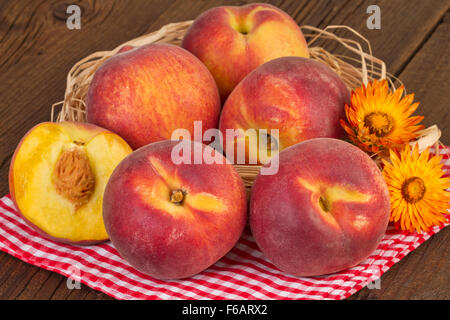 Peaches on red checkered tablecloth - Stock Photo