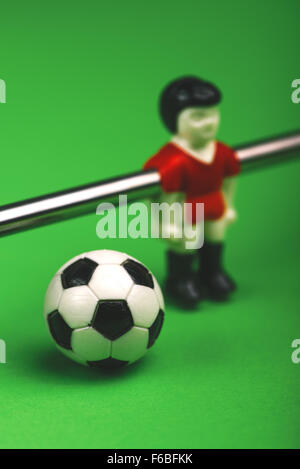 Table soccer player figurine with football, selective focus - Stock Photo