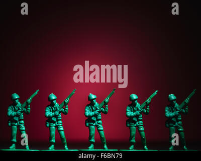 Several plastic soldiers in row, red background - Stock Photo