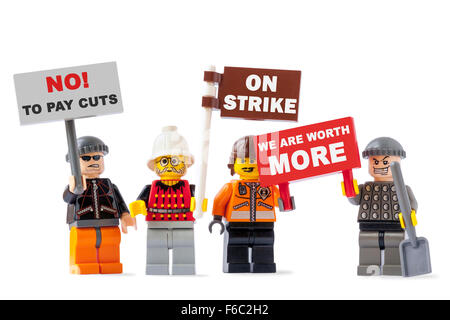 Workers on strike concept with four toy figurines isolated on white background and holding signs with protest messages - Stock Photo