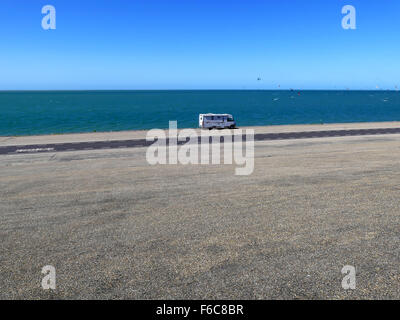 Camper motor home on deserted road with blue sky and many kites - Stock Photo
