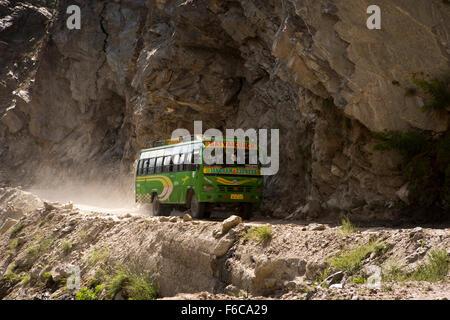 India, Himachal Pradesh, Kinnaur, Akpa Khas, Satya Coach bus speeding on dusty Hindustan-Tibet Highway mountain - Stock Photo