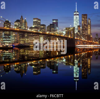 Manhattan waterfront reflected in water at night, New York City, USA. - Stock Photo