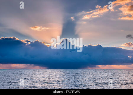 Tropical storm with dark cloud and dramatic sun rays shining through on ocean off the coast of Key West, Florida - Stock Photo