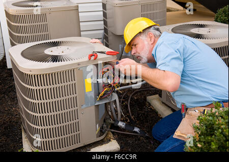 Mature Repairman Works On Apartment Air Conditioning Unit - Stock Photo
