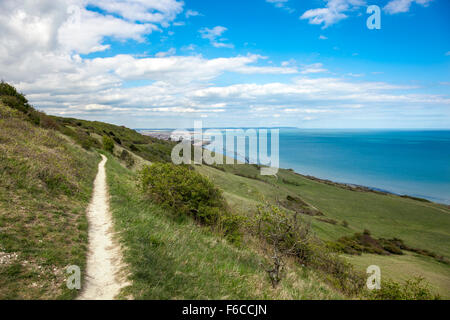 A hiking path in Beachy Head with Eastbourne in the far back, England - Stock Photo