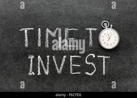 time to invest phrase handwritten on chalkboard with vintage precise stopwatch used instead of O - Stock Photo