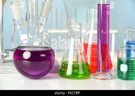Laboratory glassware with different colored liquids on white table - Stock Photo