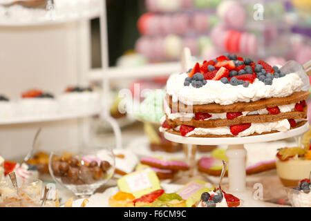 Delicious biscuit cake with strawberries and blueberries on sweet table for wedding party - Stock Photo