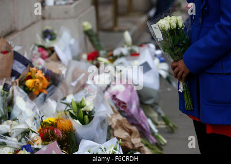 London, UK. 16th Nov, 2015. A woman prepares to lay flowers outside the Embassy of France in London, UK, Monday, - Stock Photo