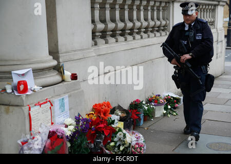 London, UK. 16th Nov, 2015. An armed police officer patrols near flowers, laid for the dead after the shooting in - Stock Photo