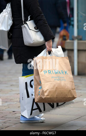 A woman carrying multiple branded shopping bags, River Island & Primark, on Market St. Piccadilly, Manchester, Uk - Stock Photo