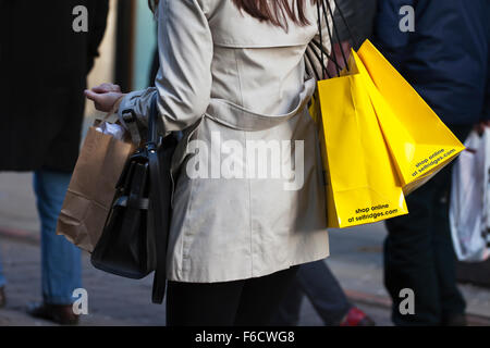 Shop online; A woman carrying yellow multiple branded Selfridges shopping bags on Market St. Piccadilly, Manchester, - Stock Photo