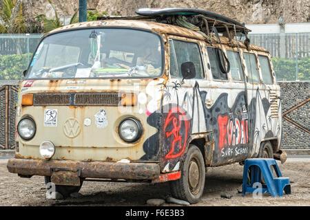 LIMA, PERU - OCTOBER 12, 2014: Rusty Volkswagen van wreck used as a surfboard equipment storage, seen in Lima Beach, - Stock Photo