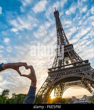 Hands forming heart, sunset behind Eiffel Tower, Champ de Mars, Paris, Ile-de-France, France - Stock Photo