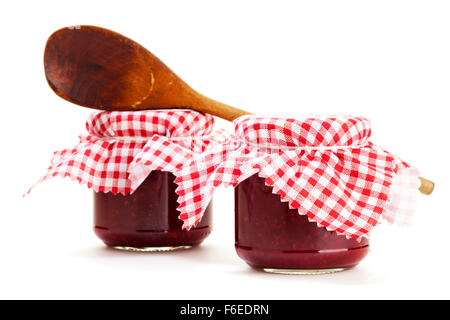 Two jars of homemade jam and wooden cooking spoon isolated on white background - Stock Photo