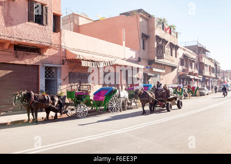 Horse-drawn carriages, donkey cart and moped on Marrakesh main street - Stock Photo