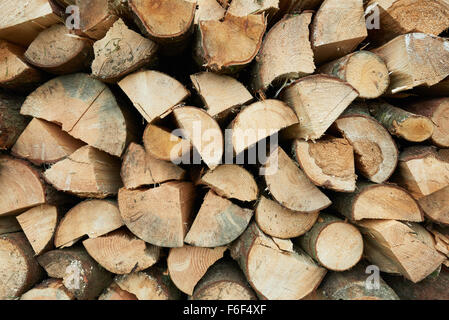 Background of dry chopped firewood logs in a stack - Stock Photo