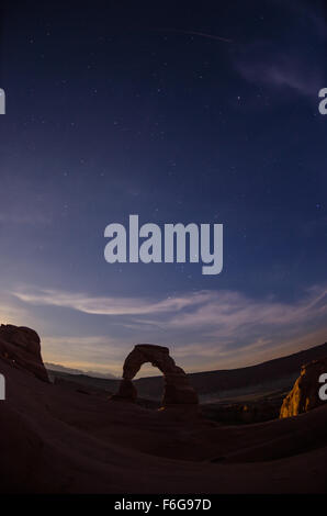 The silhouette of delicate arch as night falls over the desert with a fisheye lens - Stock Photo