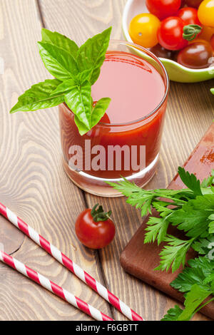 Fresh tomato juice smoothie with basil on wooden table - Stock Photo