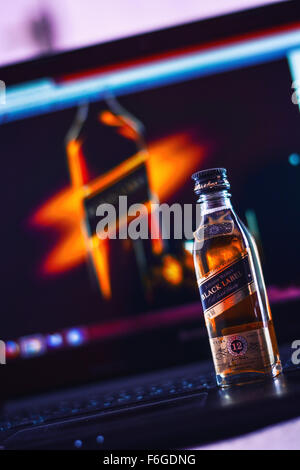 A small bottle of black label alcohol kept on a laptop with an image of the same bottle. - Stock Photo