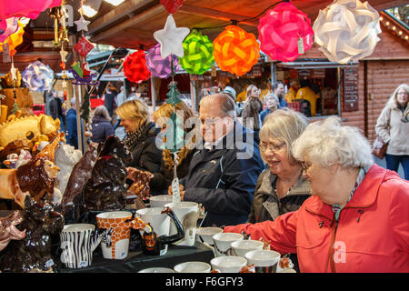 Manchester Christmas market stall busy with elderly female visitors looking at Christmas decorations - Stock Photo