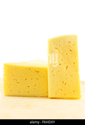 Yellow cheese photographed close up on a white background - Stock Photo