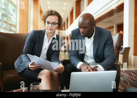 Portrait of young business woman and man sitting at hotel lobby discussing papers. Business people meeting in coffee - Stock Photo