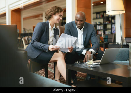 Young business people discussing important documents. Diverse business team meeting in a hotel lobby working on - Stock Photo