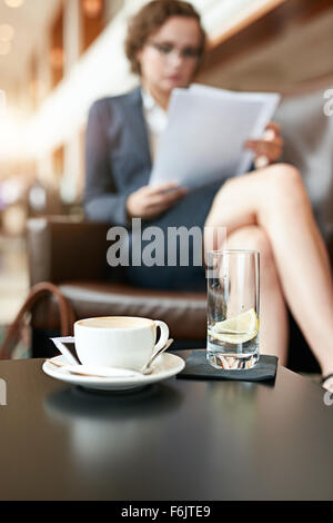 Cup of coffee and glass of water on cafe table with businesswoman sitting in background reading documents. - Stock Photo