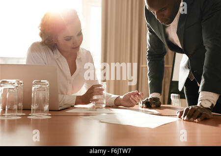 Two young business colleagues working on some business ideas. Entrepreneurs analyzing business reports on conference - Stock Photo