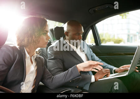 Shot of young business associates travelling to work in the luxury car on the back seat working on laptop. Discuss - Stock Photo