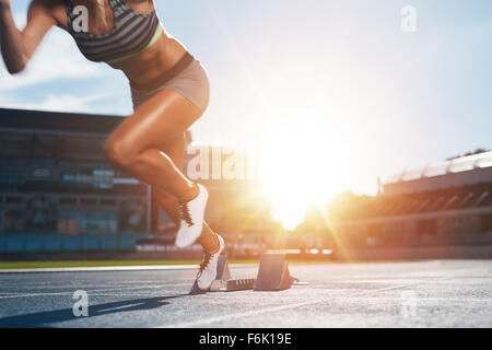 Cropped shot of young female athlete launching off the start line in a race. Female runner started the sprint from - Stock Photo