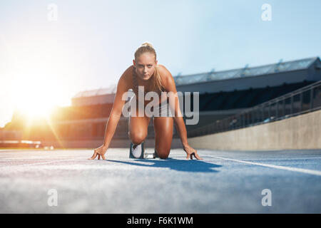 Confident young female athlete in starting position ready to start a sprint. Woman sprinter ready for a run on racetrack - Stock Photo