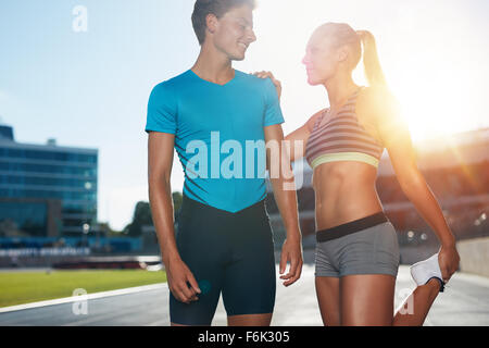 Young runner stretching her legs before a track event. Two young runners on a sunny day practicing at athletics - Stock Photo