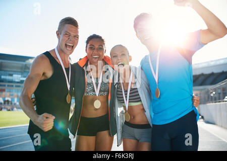 Portrait of ecstatic young runners with medals celebrating success in athletics stadium. Young men and women looking - Stock Photo