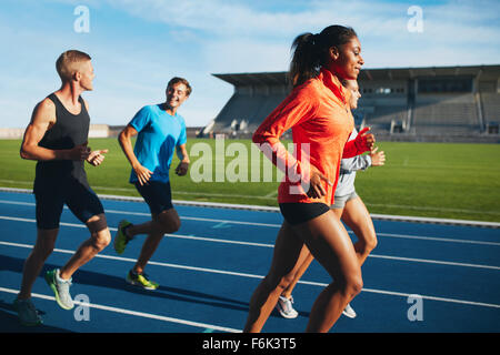 Fit men and women running on a race track. Multiracial athletes practicing on race track in stadium. - Stock Photo